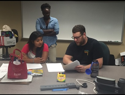 QESST Scholar Alex Routhier working    with a CompuGirl while RET Rebecca Hooper observes.